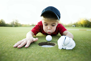 boy on golf course trying to blow golf ball into hole